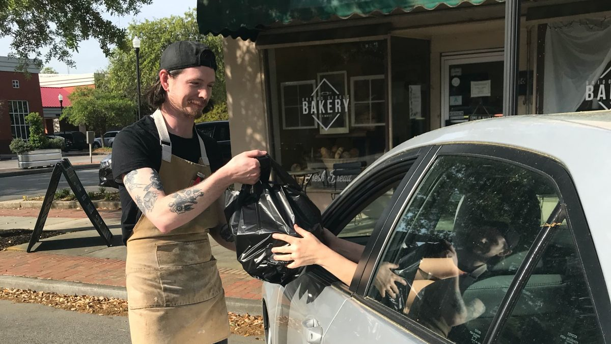 A customer receives their curbside pickup from Brad at Griggs Circle Bakery