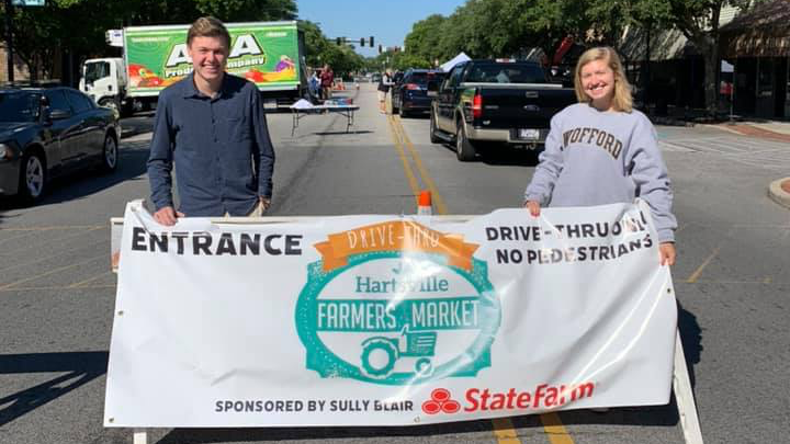 Volunteers hold a banner at the Hartsville Farmers Market Drive Thru event.
